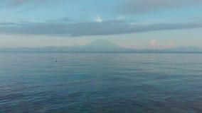 Brummengesamtlänge, die niedrig über die Wellen des Meeres gegen den Hintergrund des Vulkans Agung fliegt bali indonesien stock video