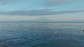 Brummengesamtlänge, die niedrig über die Wellen des Meeres gegen den Hintergrund des Vulkans Agung fliegt bali indonesien stock footage