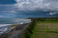 Brummenpanoramablick von Balinesereisfeldern und von vulkanischem Strand lizenzfreie stockfotos