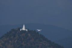 Brummenviererkabel-Hubschrauberfliegen und Schweben im Landschaftshintergrund Lizenzfreie Stockfotos