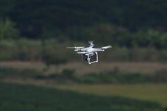 Brummenviererkabel-Hubschrauberfliegen und Schweben im Landschaftshintergrund Lizenzfreie Stockfotografie