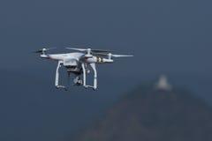 Brummenviererkabel-Hubschrauberfliegen und Schweben im Landschaftshintergrund Lizenzfreies Stockfoto