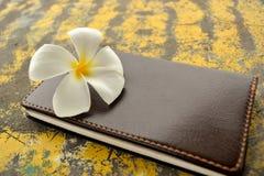Brun anteckningsbok med den vita Frangipaniblomman Royaltyfria Bilder