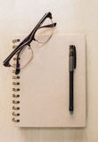 Brun anteckningsbok med glasögon och svart penna på wood bakgrund royaltyfri fotografi
