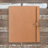 Brun anteckningsbok på tappningträbakgrund arkivbilder