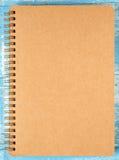 Brun anteckningsbok på blått trä Arkivfoton