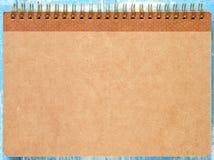 Brun anteckningsbok på blått trä Fotografering för Bildbyråer