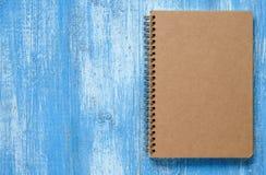 Brun anteckningsbok på blått trä Royaltyfri Bild