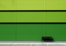Brun bänk framme av den gröna väggen Royaltyfria Bilder