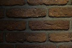 Brun bakgrund för tegelstenvägg med lågt ljus arkivfoto