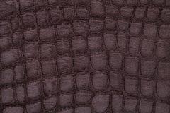 Brun bakgrund från mjukt stoppningtextilmaterial, closeup Tyg med modellen som imiterar krokodilhud Royaltyfri Foto