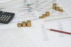 Brun blyertspenna på balansräkningen med moment av guld- mynt Arkivfoto