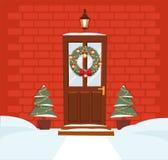 Brun dörr för jul med kransen, snö och granar på bakgrund av ett mörkt - vägg för röd tegelsten Falsk lykta ovanför dörrskenen _ royaltyfri illustrationer