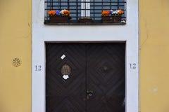 Brun dörr nummer 12 på den gula väggen Arkivbilder