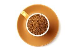 Brun elegant kopp som är full av partiklar för ögonblickligt kaffe, tefat under den Sikten från över, så det gör perfekt rund for Royaltyfri Foto