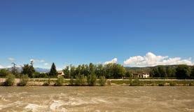 Brun flod och blå himmel arkivfoto