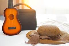 Brun floopy hatt med bandet, den lilla gitarrleksaken och resväskabac royaltyfria bilder