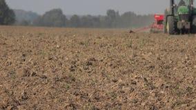 Brun fältjord och den suddiga traktoren med seederen arbetar på bakgrund 4K lager videofilmer