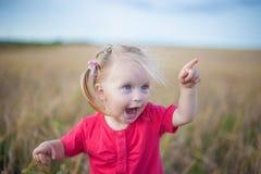 Brun hårflicka som spelar i rågfältet Arkivfoto