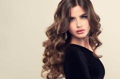 Brun haired kvinna med den omfångsrika, skinande och lockiga frisyren Burrigt hår arkivfoto