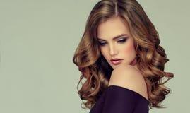 Brun haired kvinna med den omfångsrika, skinande och lockiga frisyren Burrigt hår arkivbilder