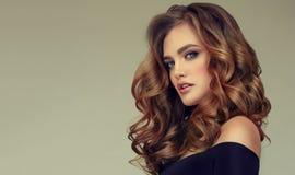 Brun haired kvinna med den omfångsrika, skinande och lockiga frisyren Burrigt hår arkivbild