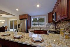 Brun kökdesign med mahognyköksskåp fotografering för bildbyråer