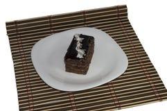 Brun kaka med pärlor på en platta, på en brun filt Royaltyfri Foto