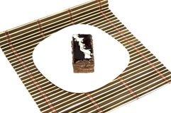 Brun kaka med pärlor på en vit platta, på en brun filt Arkivfoton