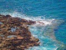 Brun karg stenig kust med ljusa blåa vågor som bryter på den arkivfoton