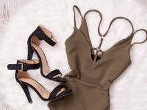 Brun klänning och svarta skor på vit päls, trendigt begrepp Arkivbilder