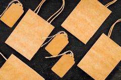 Brun kraft pappers- påse för att shoppa nära prislappar på svart modell för bästa sikt för bakgrund Arkivbilder