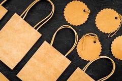 Brun kraft pappers- påse för att shoppa nära prislappar på svart modell för bästa sikt för bakgrund Royaltyfria Foton