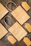 Brun kraft pappers- påse för att shoppa nära prislappar på trämodell för bästa sikt för bakgrund Arkivbilder