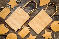 Brun kraft pappers- påse för att shoppa nära prislappar på trämodell för bästa sikt för bakgrund Royaltyfria Foton
