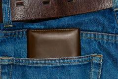Brun läderhandväska i facket Plånbok halvvägs ut från jeans tillbaka Fick- jeans med plånbokbrunt Royaltyfri Fotografi