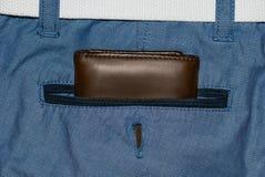 Brun läderhandväska i facket Plånbok halvvägs ut från jeans tillbaka Fick- jeans med plånbokbrunt Arkivbild