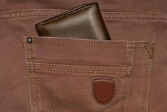 Brun läderhandväska i facket Plånbok halvvägs ut från jeans tillbaka Fick- jeans med plånbokbruntfärg Arkivfoto