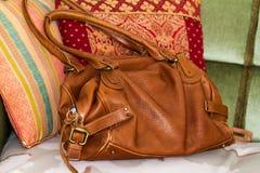 Brun läderhandväska på en plats med kuddar Royaltyfri Foto