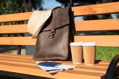 Brun läderpåse med hatten, pass med biljetter, översikt och pappers- koppar på träbänk Royaltyfri Foto