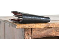 Brun läderplånbok på trätabellen, vit bakgrund Arkivfoto