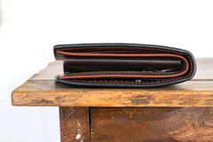 Brun läderplånbok på trätabellen, vit bakgrund Royaltyfria Bilder