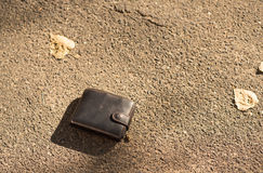 Brun läderplånbok på trottoaren Royaltyfria Foton