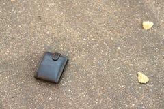 Brun läderplånbok på trottoaren Arkivfoton