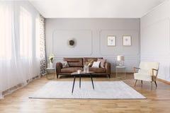 Brun lädersoffa i vardagsruminre med den stilfulla fåtöljen, kaffetabellen och teckningar royaltyfri bild