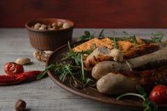 Brun maträtt med grillade korvar med senap och arugula arkivfoton