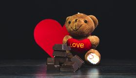 Brun nallebjörn, smaskig choklad och svart bakgrund och valentin dag royaltyfria foton