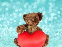 Brun nallebjörn som rymmer stor röd hjärta arkivfoton