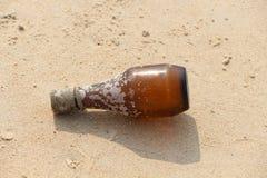 Brun plast- botttle på en strand av Goa Arkivbilder
