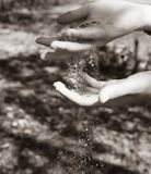 Brun sand i händerna royaltyfri foto